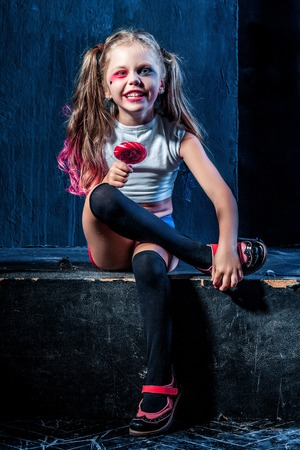 crazy girl: The funny crazy girl with candy on dark background