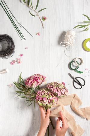 Las manos de floristería en contra de escritorio con herramientas de trabajo y las cintas sobre fondo de madera Foto de archivo - 63980410