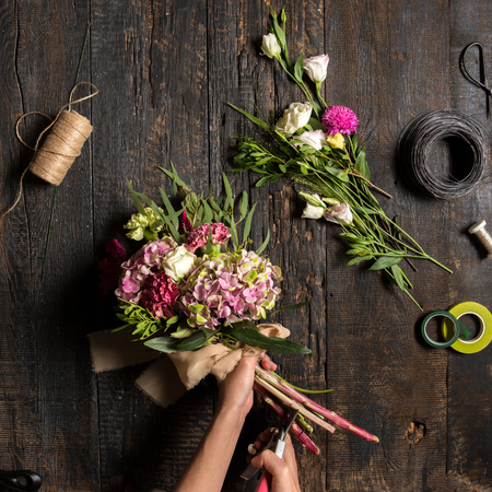 The hands of florist against desktop with working tools and ribbons on wooden background Imagens