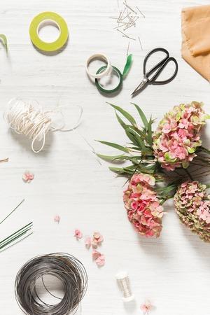 白い木製の背景の作業ツールと花屋デスクトップ