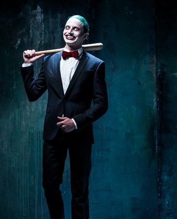 Bloody Halloween theme: The crazy joker face on black background with baseball bat