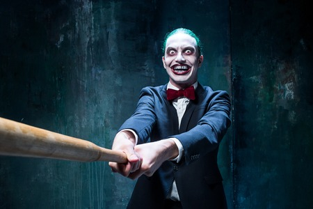 psychopath: Bloody Halloween theme: The crazy joker face on black background with baseball bat