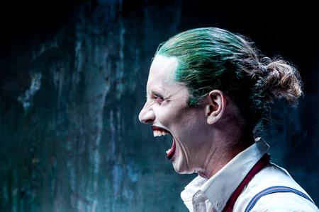 Bloody Halloween theme: The crazy joker face on black background Stock Photo
