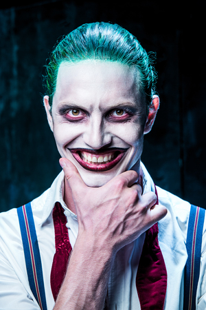 Bloody Halloween theme: The crazy joker face on black background Stock Photo