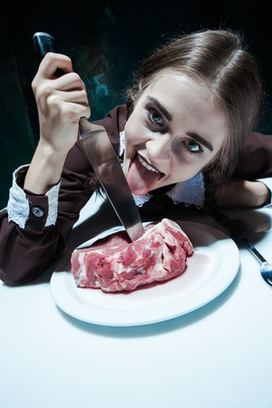 Portrait of a young girl with knife and and a piece of raw meat on a plate. Girl in school uniform as killer. The image in the style of Halloween and Addams family Фото со стока