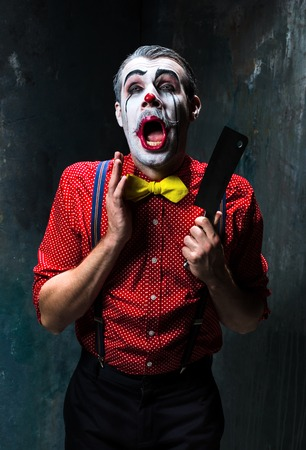 scary clown: The scary clown holding a knife on dack. Halloween concept of horror and murderer Stock Photo