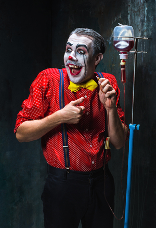 scary clown: The scary clown and drip with blood on dack. Halloween concept of horror and murderer Stock Photo