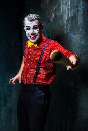 scary clown: The scary clown and baseball-bat on dack. Halloween concept of horror and murderer