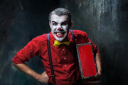 terrible: Terrible clown and Halloween theme: Crazy red clown with suitcase on a dark background Stock Photo