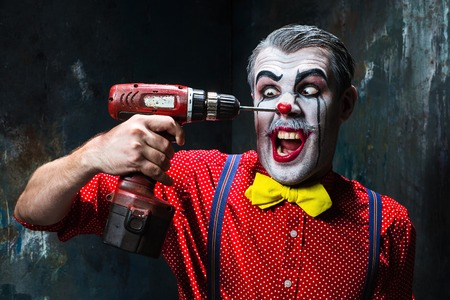 electric drill: The scary clown and electric drill on dack. Halloween concept of horror and murderer