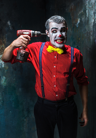 scary clown: The scary clown and electric drill on dack. Halloween concept of horror and murderer