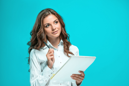 Smiling young business woman with pen and tablet for notes on a blue background
