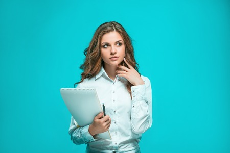 mujeres pensando: The thoughtful young business woman with pen and tablet for notes on a blue background
