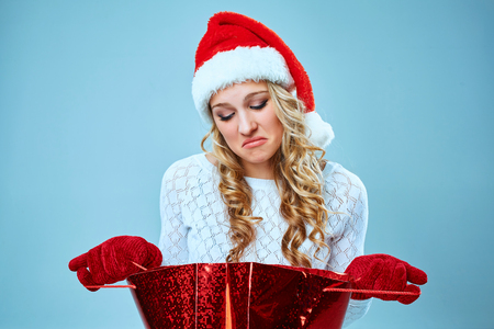 Frustrated and annoyed beautiful young woman in Santa Claus hat with a gift on a blue background