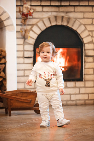 casua: The happy child little girl standing at home against fireplace