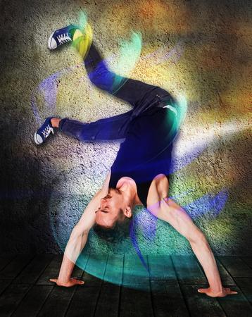 La parada de manos bailarín de la rotura haciendo contra el fondo de la pared colorida