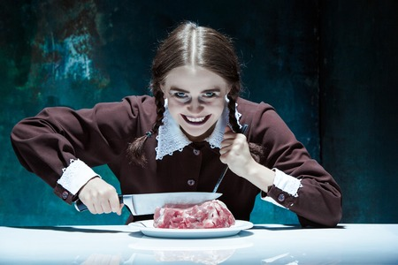 Portrait of a young girl with knife, fork and and a piece of raw meat on a plate. Girl in school uniform as killer. The image in the style of Halloween and Addams family Stock Photo