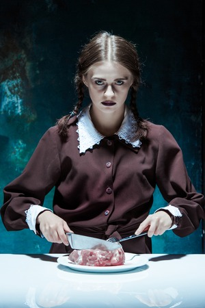 girl with knife: Portrait of a young girl with knife, fork and and a piece of raw meat on a plate. Girl in school uniform as killer. The image in the style of Halloween and Addams family Stock Photo