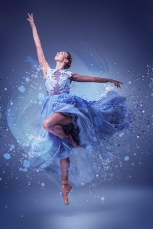 La belle danse de ballerine dans la longue robe bleue sur fond bleu