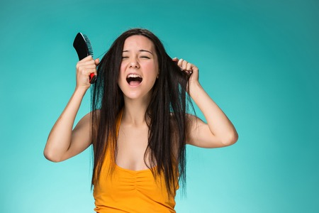 bad hair: Frustrated young woman having a bad hair on blue Stock Photo