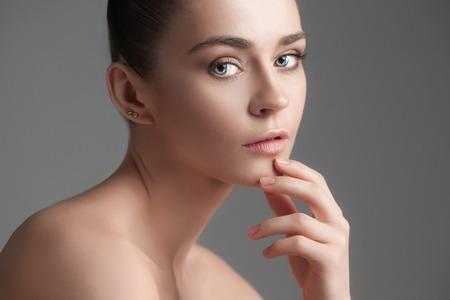 La hermosa cara femenina. La piel perfecta y limpia de la cara en gris