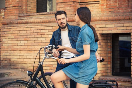 opposite: Young couple sitting on a bicycle opposite the city