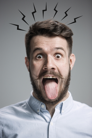 denote: The tongue hanging out man on the gray background. concept of extreme mental stress