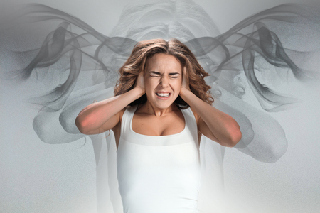 sicken: The young womans portrait with pain emotions on gray background. Concept headache