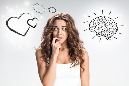 灰色の背景におびえた感情を持つ若い女性の肖像画。五感と心の間の選択の概念