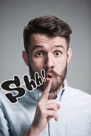 shh: Man wearing a blue shirt is looking wary and saying Shh. Over gray background