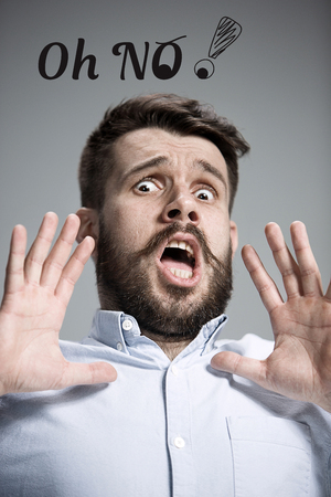 Man wearing a blue shirt in a fright and saying Oh No over gray background
