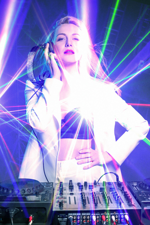 Beautiful blonde DJ girl in a white suit on decks on the party on the blue background