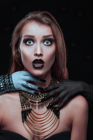 imminence: Closeup portrait of a pretty gothic woman with hands of vampire on her neck on black background Foto de archivo