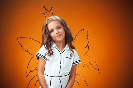 The cute cheerful little girl portrait on orange background Stock Photo