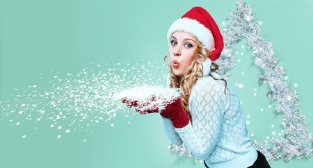 Mooie jonge vrouw in de kleren van de Kerstman met sneeuwvlokken op een blauwe achtergrond Stockfoto