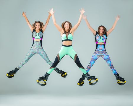 The group of young girls, jumping on kangoo training on gray Stock fotó