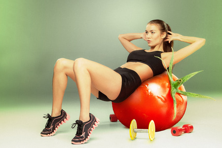 lifestile: Sporty woman doing aerobic exercise on a tomato as fitness ball. Concept of diet and healthy foods and lifestile Stock Photo