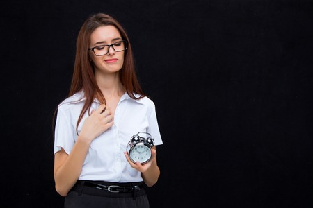 lateness: The young business woman in glasses with alarm clock on a black background