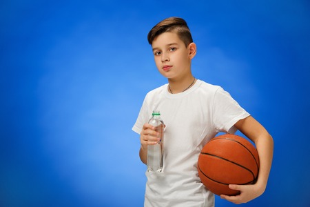 11 year old: Adorable 11 year old boy child with basketball ball drinking water on blue background.