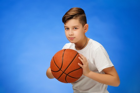 11 year old: Adorable 11 year old boy child with basketball ball on blue background.