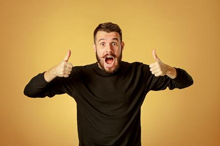 Portret van een jonge man met geschokte gelaatsuitdrukking over oranje achtergrond studio