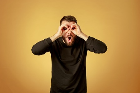 Portrait of young man with shocked facial expression over orange studio background