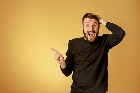 Portrait of young man with shocked facial expression pointing to the left over orange studio background