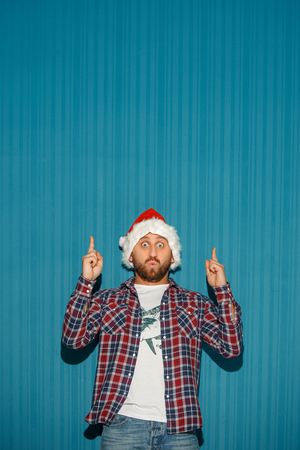 The surprised christmas man wearing a santa hat showing anything on the blue studio background