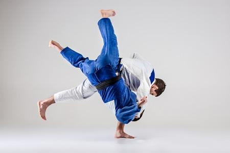 De twee judokasvechters die mannen op grijze studioachtergrond bestrijden Stockfoto