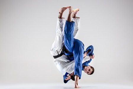 The two judokas fighters fighting men on gray studio background Stock fotó