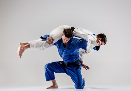 The two judokas fighters fighting men on gray studio background Stock Photo