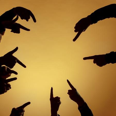Molte sagome di mani che puntano avanti o fuori o dentro su sfondo arancione