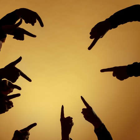 Many silhouettes of hands pointing ahead or out or inside on orange background