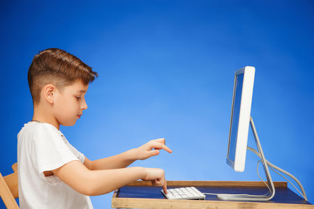 School-age boy sitting in front of the monitor laptop at blue studio backgroubd Stock Photo